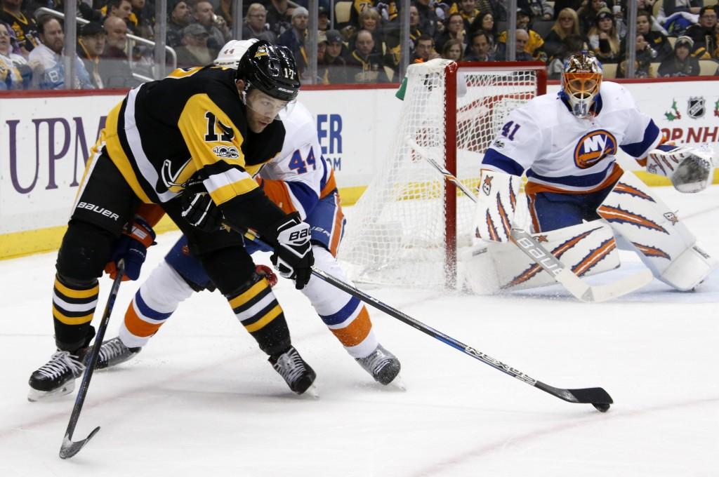 Pittsburgh Penguins' Bryan Rust (17) gets off a centering pass with New York Islanders' Calvin de Haan (44) defending in front of goalie Jaroslav Hala