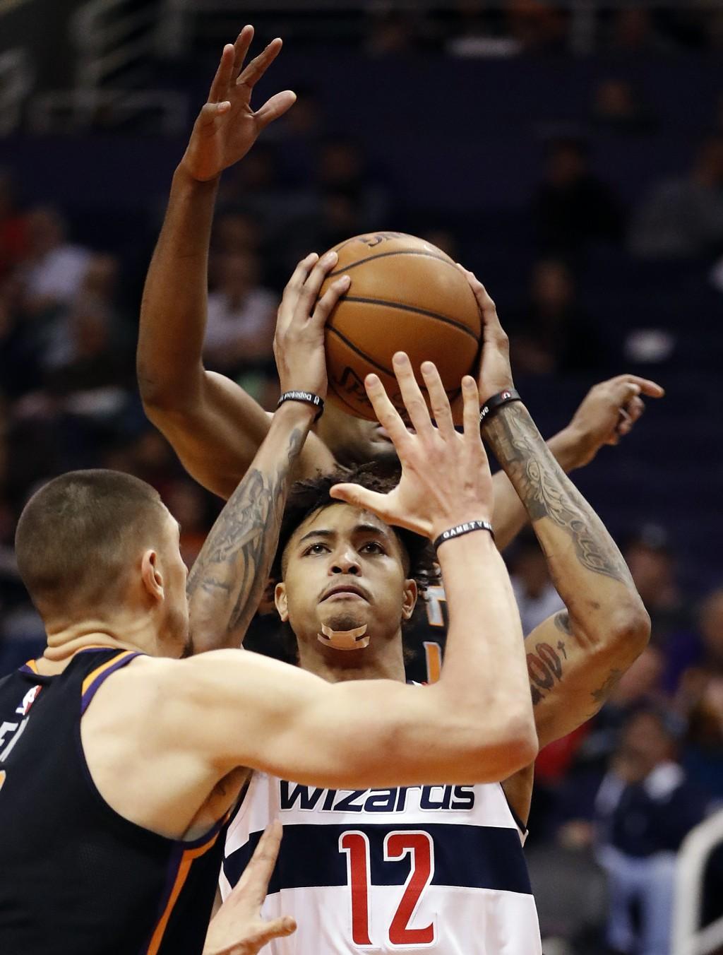 Washington Wizards forward Kelly Oubre Jr. (12) shoots over Phoenix Suns center Alex Len during the first half of an NBA basketball game, Thursday, De