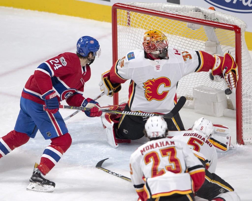 Montreal Canadiens center Phillip Danault (24) scores the second goal against Calgary Flames goalie David Rittich (33) as Flames' Sean Monahan (23) an