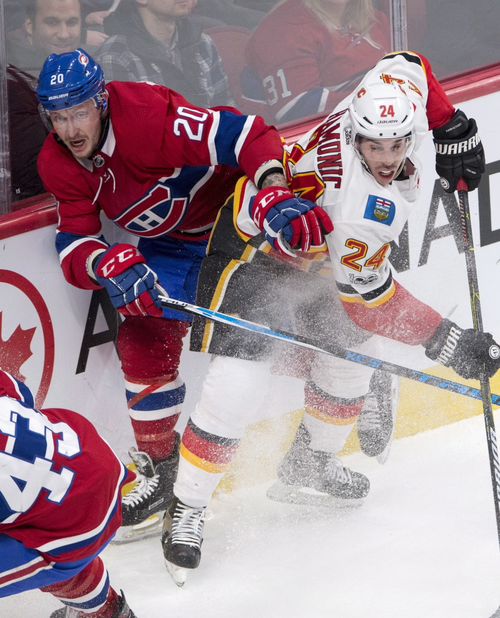Calgary Flames defenseman Travis Hamonic (24) checks Montreal Canadiens left wing Nicolas Deslauriers (20) during first-period NHL hockey  game action