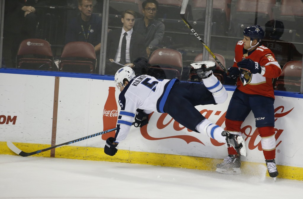Florida Panthers center Micheal Haley (18) slams Winnipeg Jets defenseman Dmitry Kulikov (5) into the boards during the first period of an NHL hockey