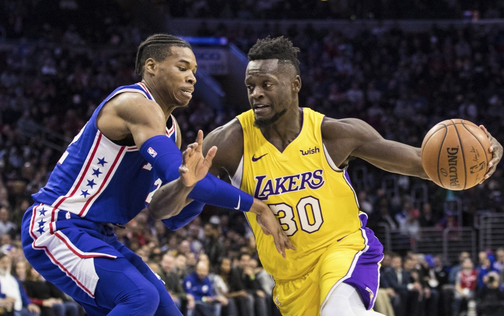 Los Angeles Lakers Julius Randle, right, drives to the basket against Philadelphia 76ers Richaun Holmes, left, during the first half of an NBA basketb