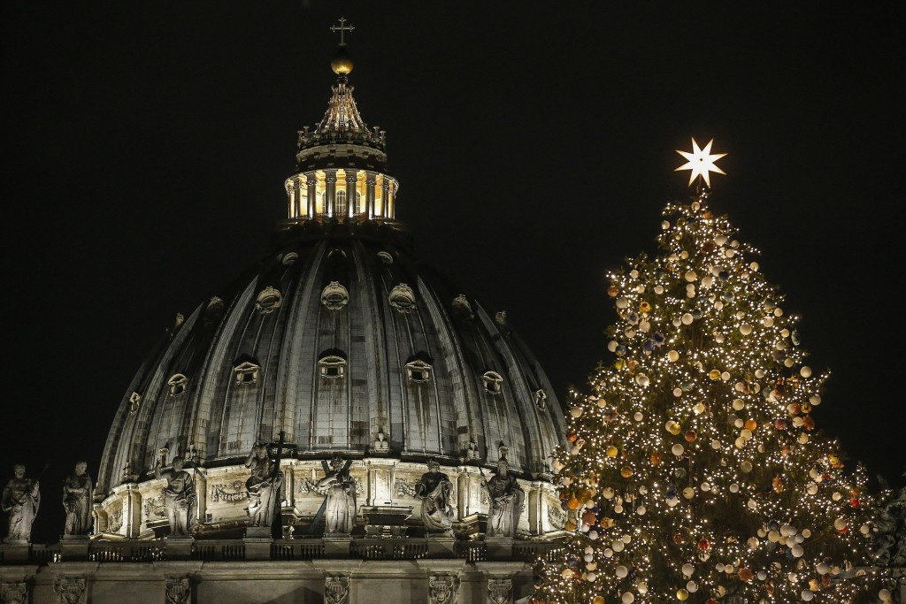 A 21 meters (69 feet) high Christmas tree coming from Poland is backdropped by the dome of St. Peter's Basilica, at the Vatican, Thursday, Dec. 7, 201