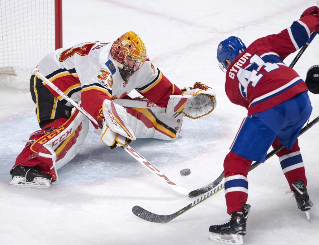 Calgary Flames goalie David Rittich (33) stops Montreal Canadiens left wing Paul Byron (41) during first-period NHL hockey  game action Thursday, Dec....