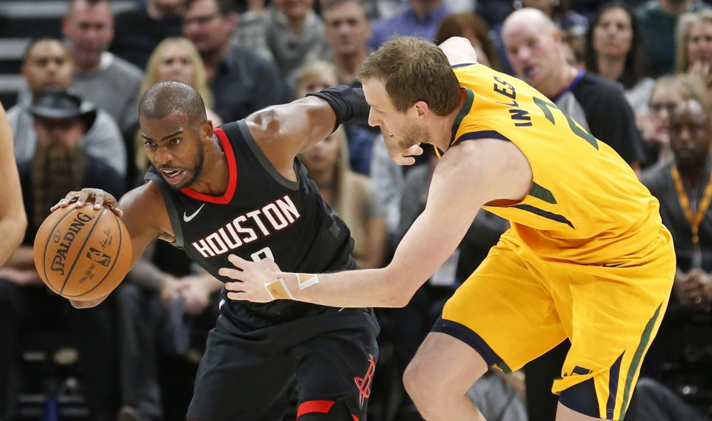 Houston Rockets guard Chris Paul, left, drives up the court as Utah Jazz forward Joe Ingles (2) defends during the first half of an NBA basketball gam