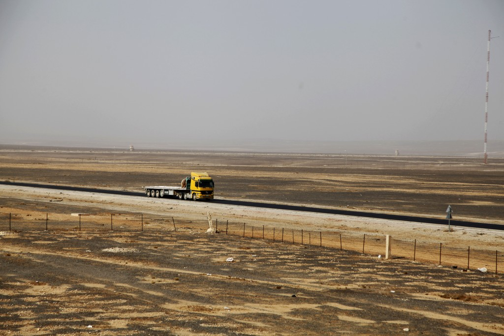 In this Nov. 27, 2017 photo, a truck drives down a bleak desert highway near the city of Azraq, Jordan where the government announced it will build a