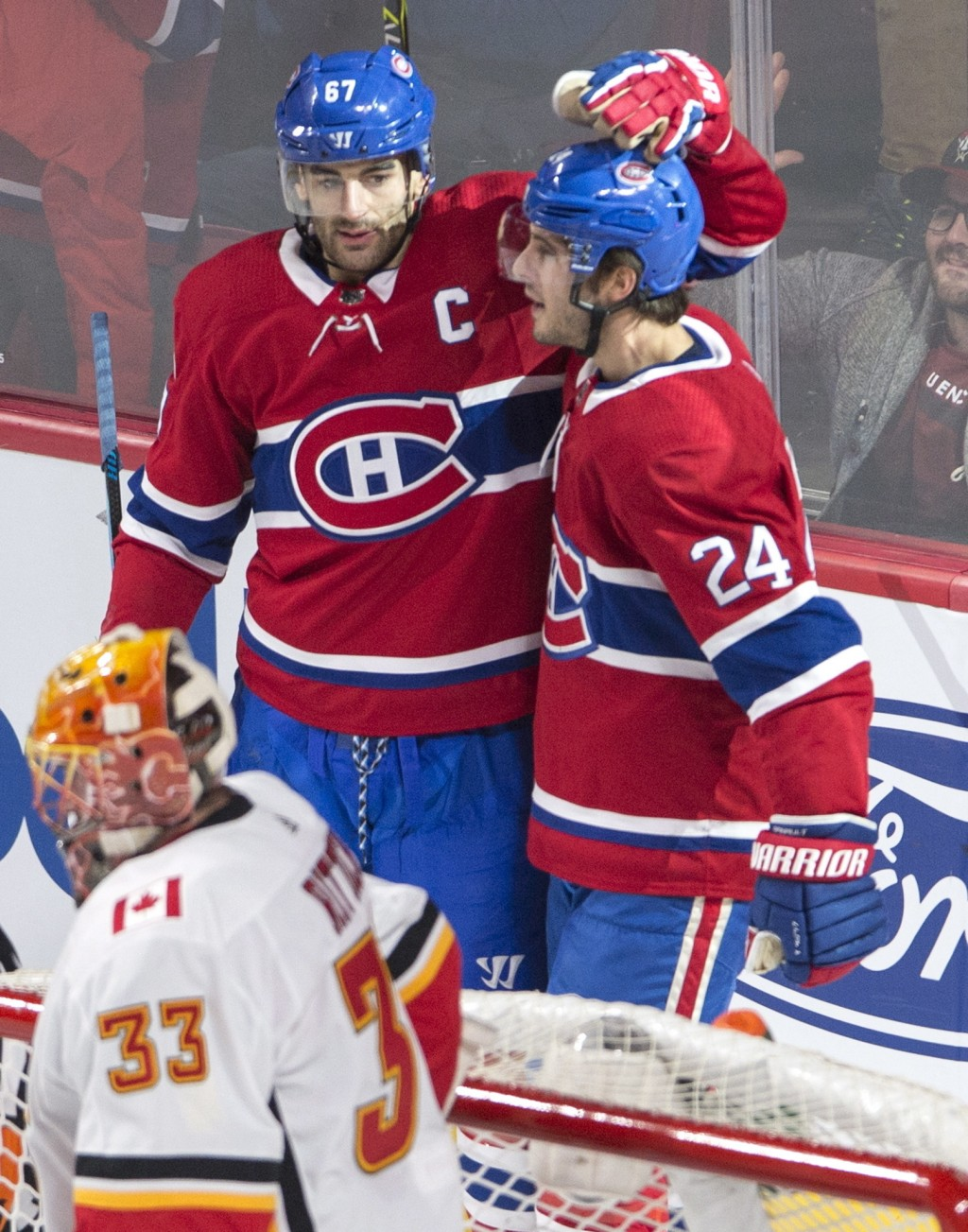 Montreal Canadiens center Phillip Danault (24) celebrates his goal with left wing Max Pacioretty (67) as Calgary Flames goalie David Rittich (33) reac