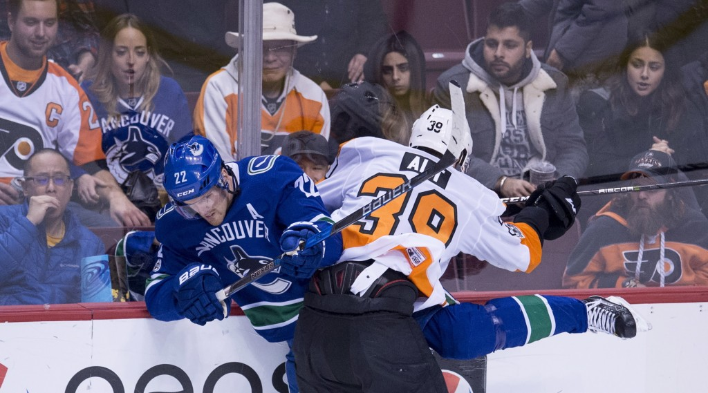 Vancouver Canucks left wing Daniel Sedin (22) is checked by Philadelphia Flyers' Mark Alt during the second period of an NHL hockey game Thursday, Dec