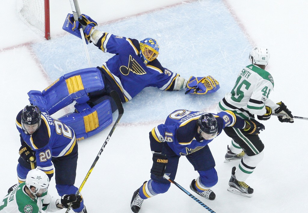 St. Louis Blues goalie Jake Allen, top left, falls while reaching for a puck as Dallas Stars' Gemel Smith (46) watches during the first period of an N
