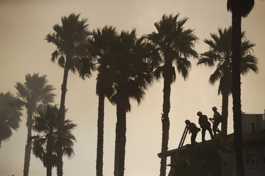 Firefighters stand on the rooftop of a beach house to water down the property while battling a wildfire at Faria State Beach in Ventura, Calif., Thurs