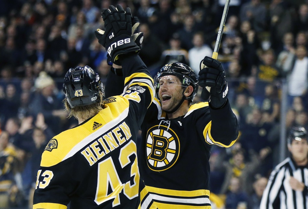Boston Bruins' David Backes (42) celebrates his goal with teammate Danton Heinen (43) during the second period of an NHL hockey game against the Arizo