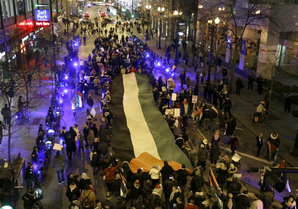 Protesters carry a large Palestinian flag as they march through the streets of Chicago's famed Loop to protest President Trump's announcement declarin