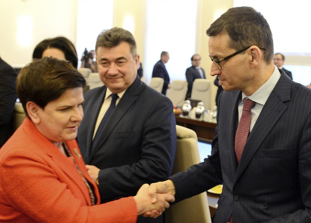 In this Dec. 5, 2017 photo Poland's Prime Minister, Beata Szydlo, left, shakes hands with Finance Minister, Mateusz Morawiecki, right, prior to a gove