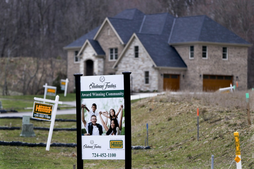 FILE - In this Monday, Feb. 27, 2017, file photo, real estate signs mark the lots near one of the new homes for sale in a development for new homes in