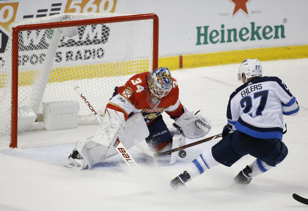 Winnipeg Jets left wing Nikolaj Ehlers (27) attempts a shot at Florida Panthers goalie James Reimer (34) during the second period of an NHL hockey gam