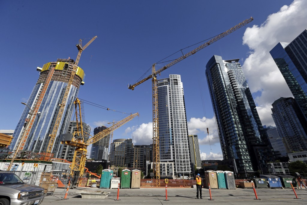 FILE - In this Wednesday, Oct. 11, 2017, file photo, construction cranes fill a block across from an Amazon building in Seattle. Seattle is among a fi...