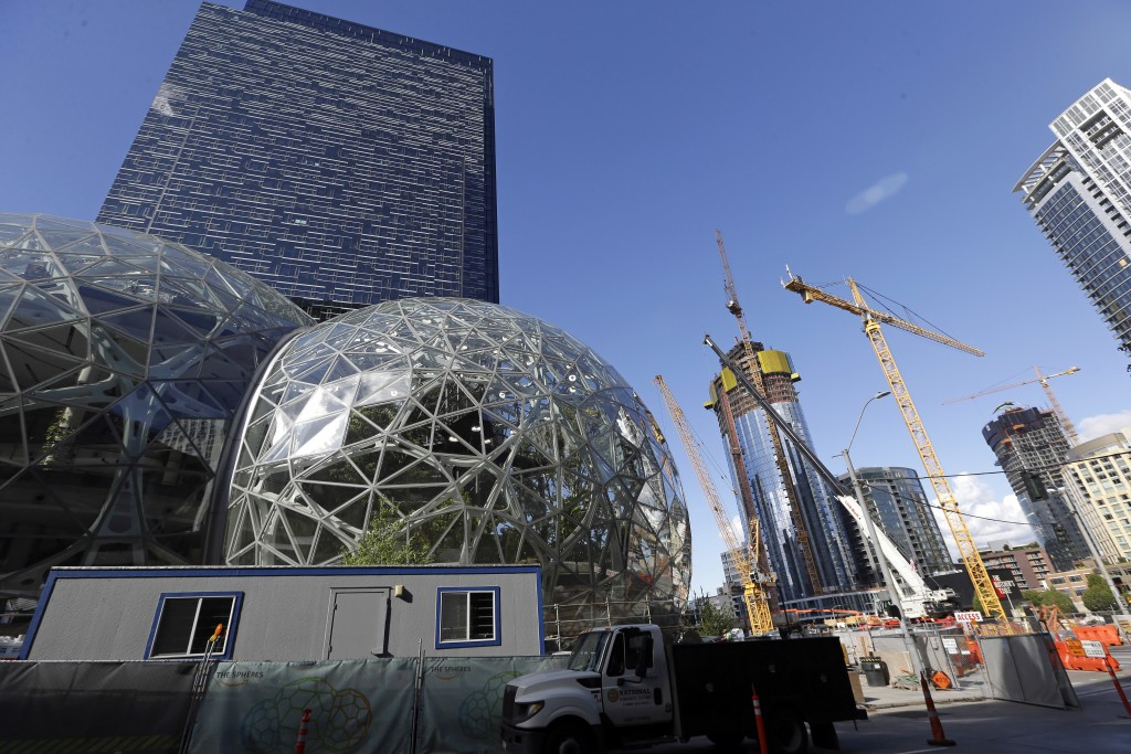 FILE - In this Wednesday, Oct. 11, 2017, file photo, large spheres take shape in front of an existing Amazon building, behind, as new construction con...