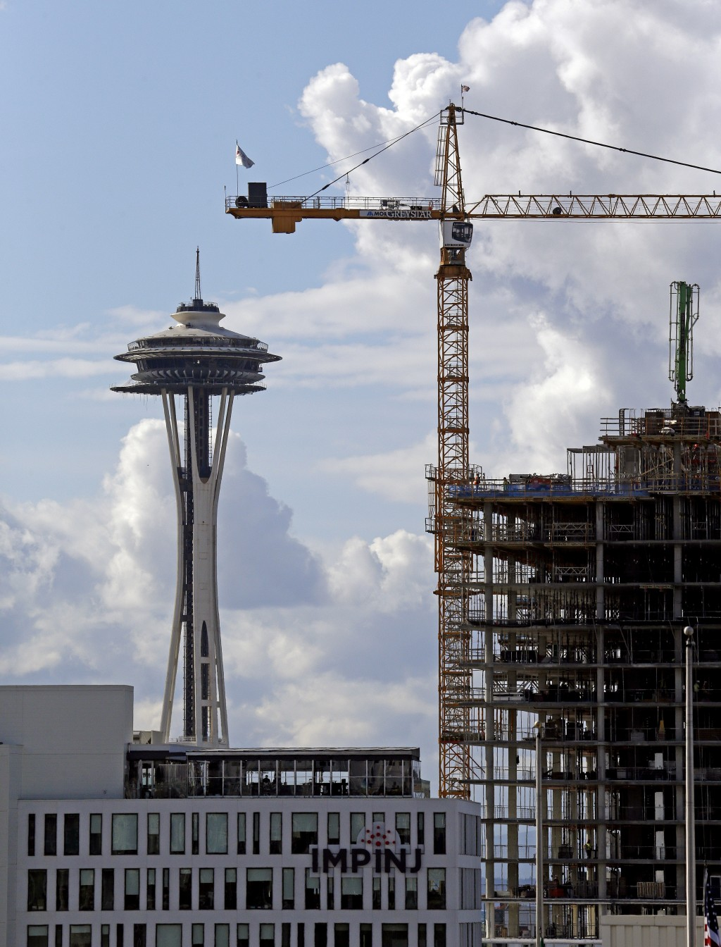 FILE - In this Wednesday, Oct. 11, 2017, file photo, a construction crane stands in view of the Space Needle in Seattle. For years now, much of downto...