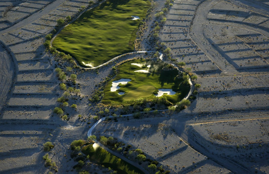 In this June 16, 2016, photo, shrubs grow on empty housing pads around a hole at the Coyote Springs golf course in the Coyote Springs development abou...