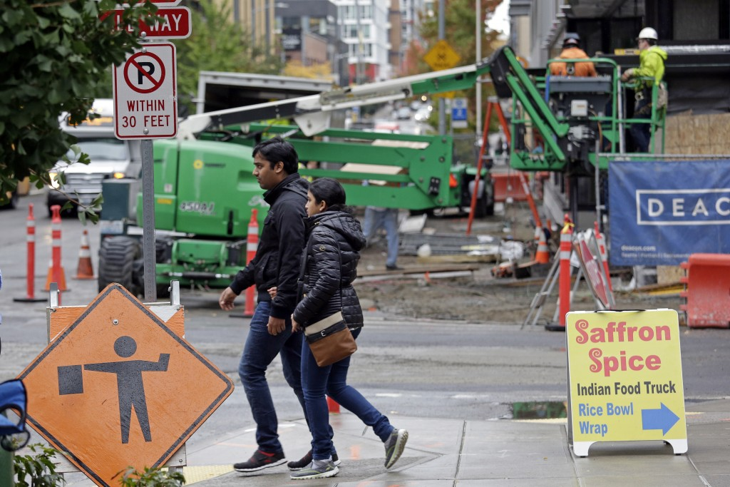 FILE - In this Tuesday, Oct. 17, 2017, file photo, pedestrians walk past a construction site near Amazon's South Lake Union headquarters in Seattle. S...