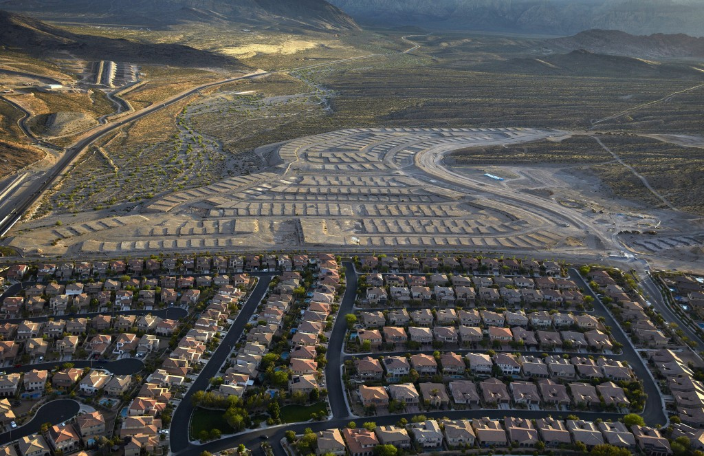 In this April 21, 2016, photo, housing lots sit empty along the western edge of Las Vegas. Some cities are still struggling to shed the scars of reces...