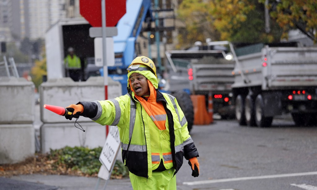 FILE - In this Tuesday, Oct. 17, 2017, file photo, construction worker Andrea Benard directs pedestrian and car traffic around a building site near Am...