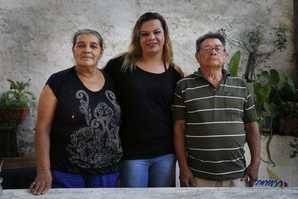 In this Nov. 2, 2017 photo, Mariana Sepulveda stands between her parents Gaspar and Isabel for a portrait at her home in Asuncion, Paraguay. The 32-ye...