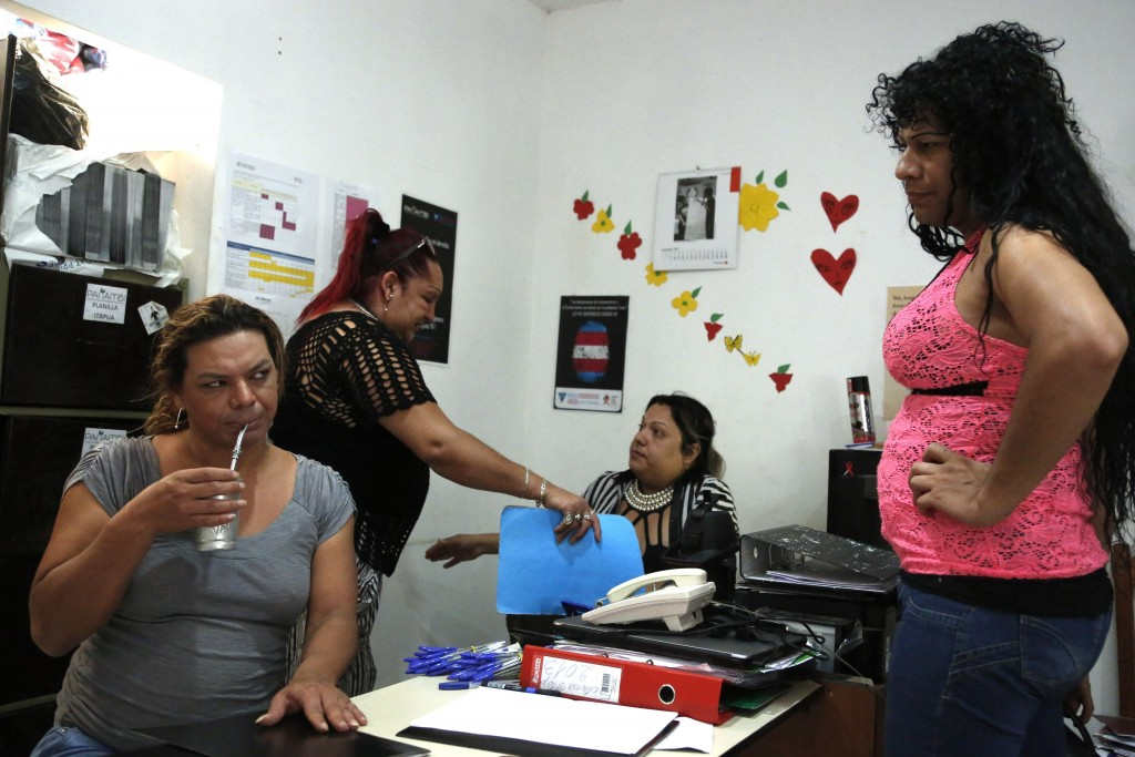 "In this Nov. 13, 2017 photo, transgender Mariana Sepulveda sips ""terere,"" a cold, herbal tea, as she works with Panambi board members Marcela Valdez,"