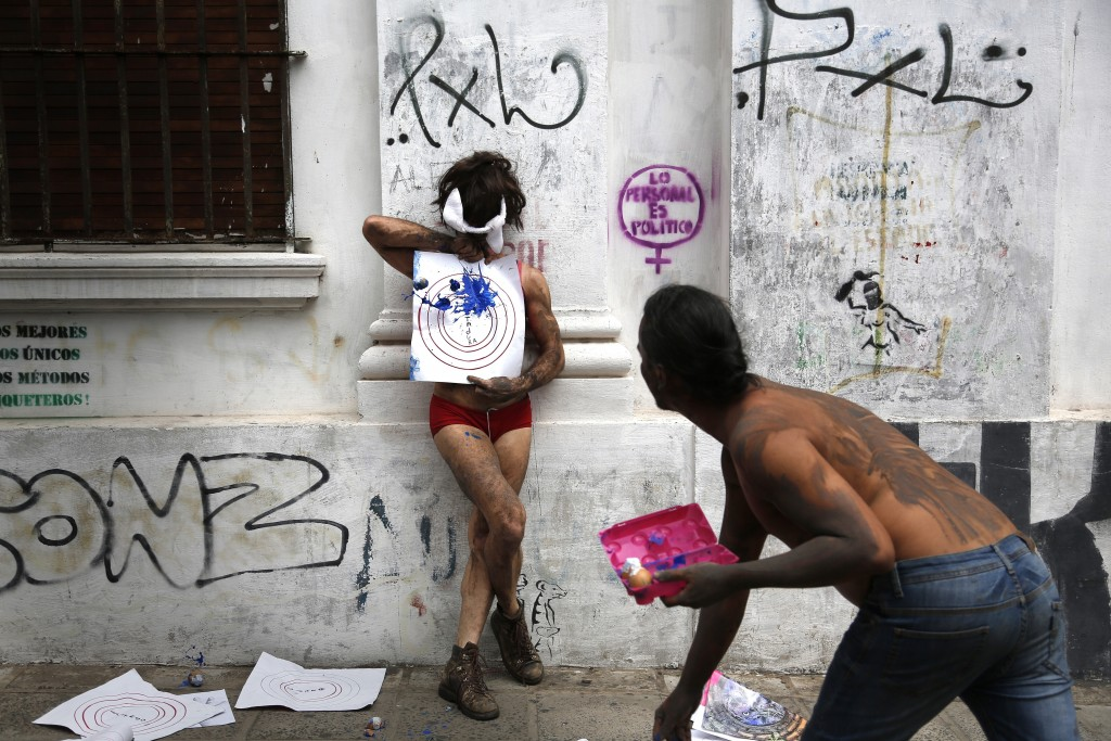 """In this Sept. 30, 2017 photo, people perform """"transvestite target practice"""" to protest the killings of transvestite prostitutes during the annual LGBQ..."""