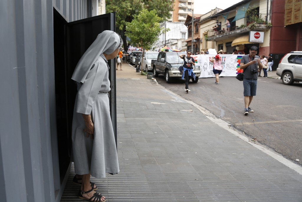 In this Sept. 30, 2017 photo, a nun watches the annual LGBQT march in Asuncion, Paraguay. A lack of legal protections and prevalent macho attitudes ha
