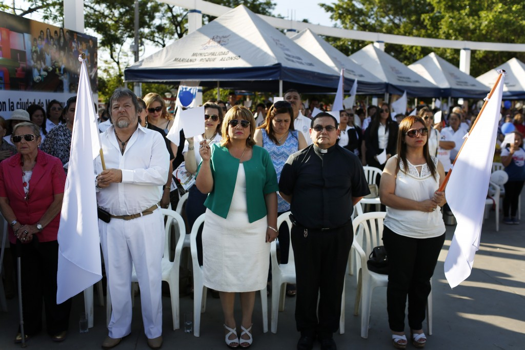 In this Oct. 28, 2017 photo, Mayor Carolina Aranda, center holding a white flag, is accompanied by members of the Catholic church during a pro-Life ce...