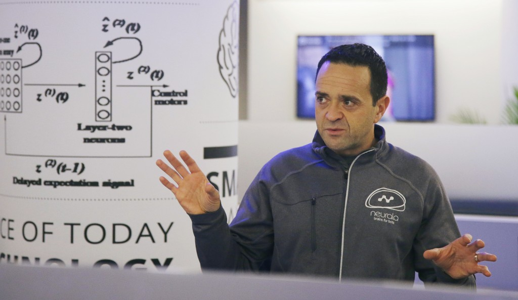 Neurala co-founder and CEO Max Versace talks with several members of his team in the company's offices, Wednesday, Dec. 13, 2017, in Boston. An artifi...