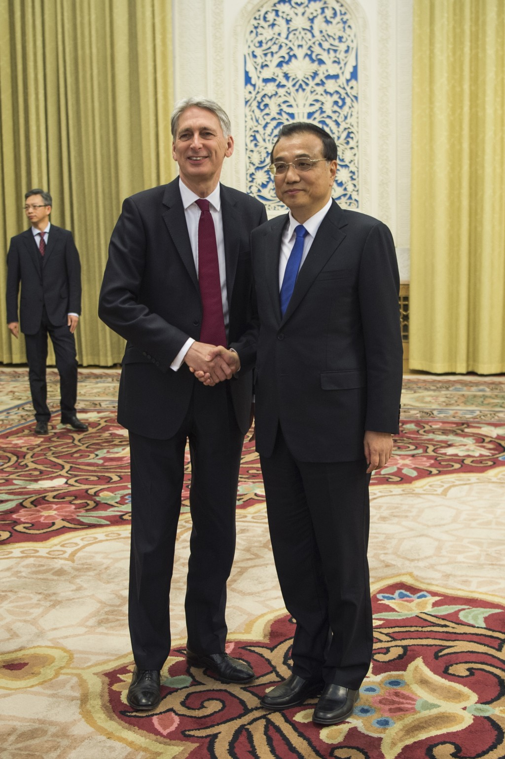 China's Premier Li Keqiang, right, meets Britain's Chancellor of the Exchequer Philip Hammond at the Great Hall of the People in Beijing, Friday, Dec.