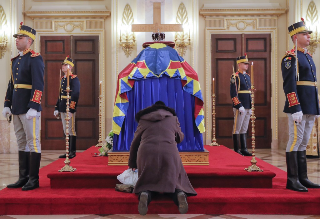 A woman kneels next to the coffin of late Romanian King Michael, at the former royal palace, in Bucharest, Romania, Thursday, Dec. 14, 2017. Thousands...