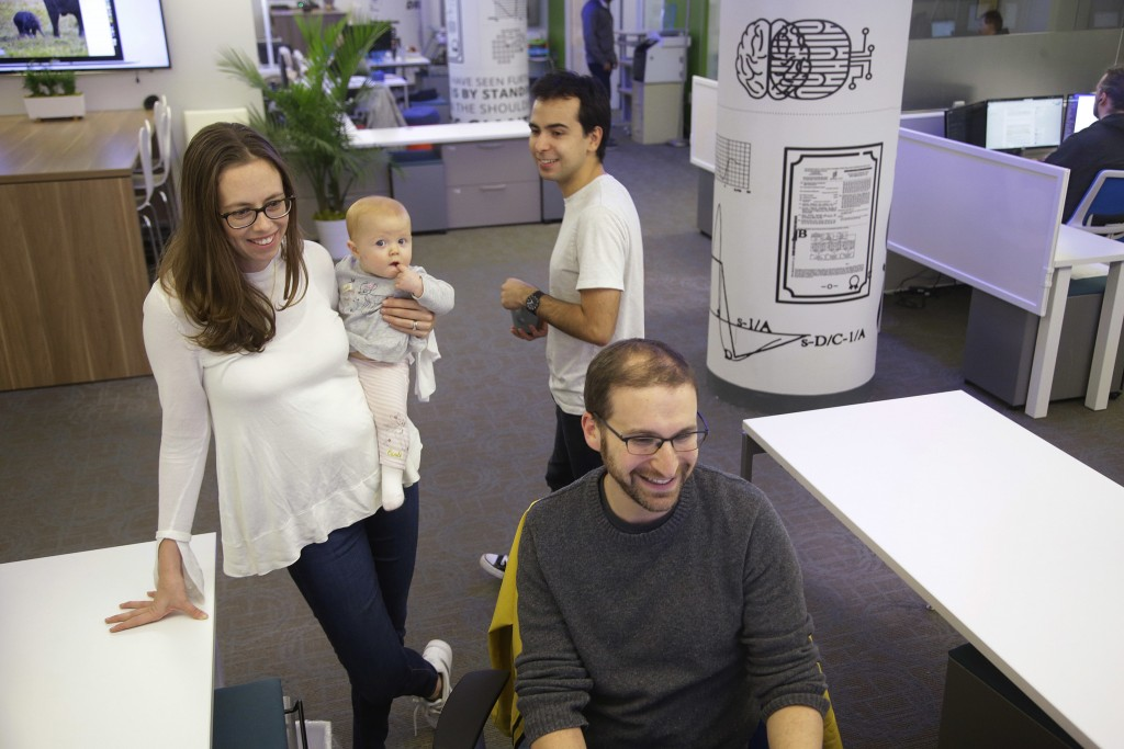 Neurala co-founder and COO Heather Ames Versace holds her daughter Aria, 6 months, as she talks with robotics engineer Lucas Neves, standing, and dire...