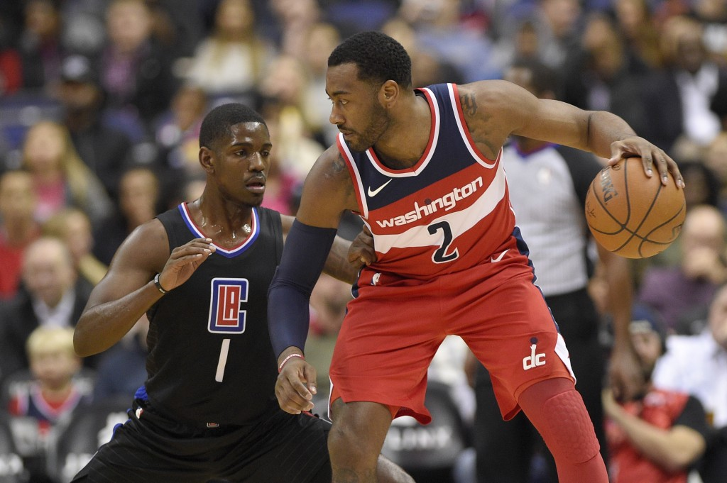 Washington Wizards guard John Wall (2) dribbles against Los Angeles Clippers guard Jawun Evans (1) during the first half of an NBA basketball game, Fr...