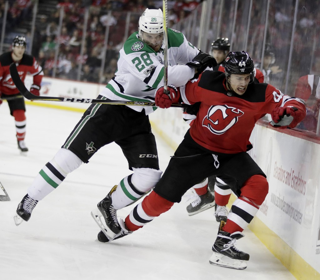 New Jersey Devils left wing Miles Wood (44) is checked by Dallas Stars defenseman Stephen Johns (28) during the second period of an NHL hockey game, F