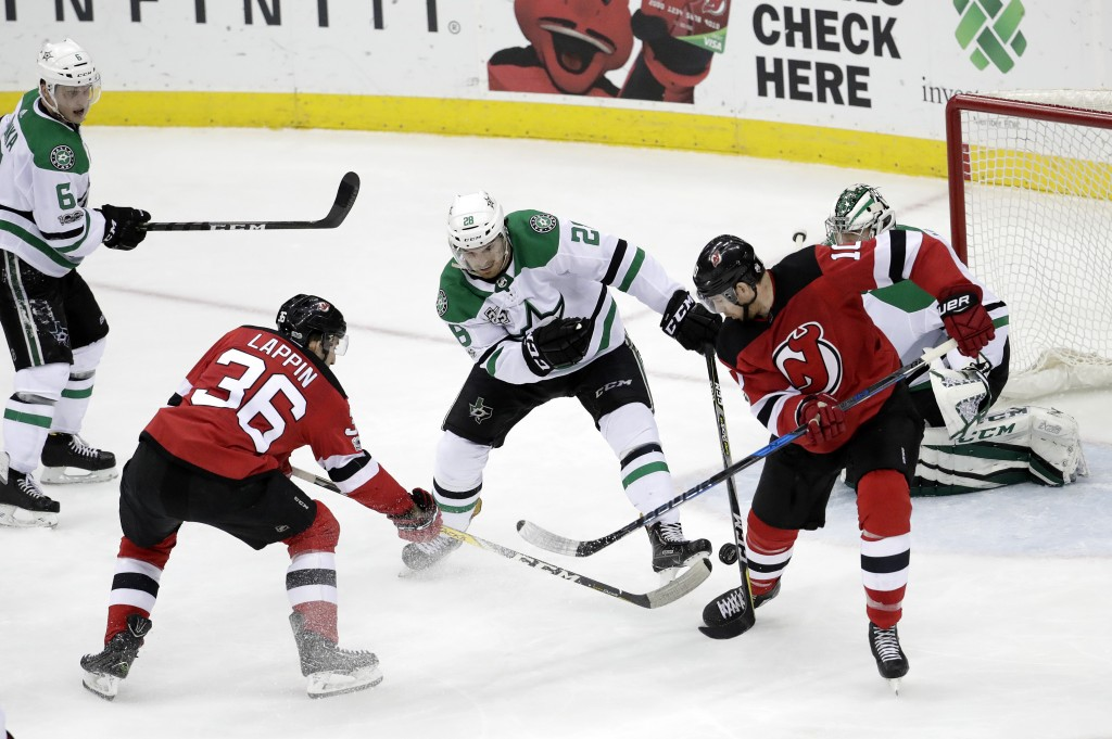 New Jersey Devils right wing Nick Lappin (36) gets his shot through the defense of Dallas Stars defenseman Stephen Johns (28) and goalie Kari Lehtonen