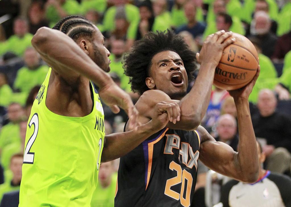 Phoenix Suns forward Josh Jackson (20) drives against Minnesota Timberwolves forward Andrew Wiggins (22) in the first quarter of an NBA basketball gam...