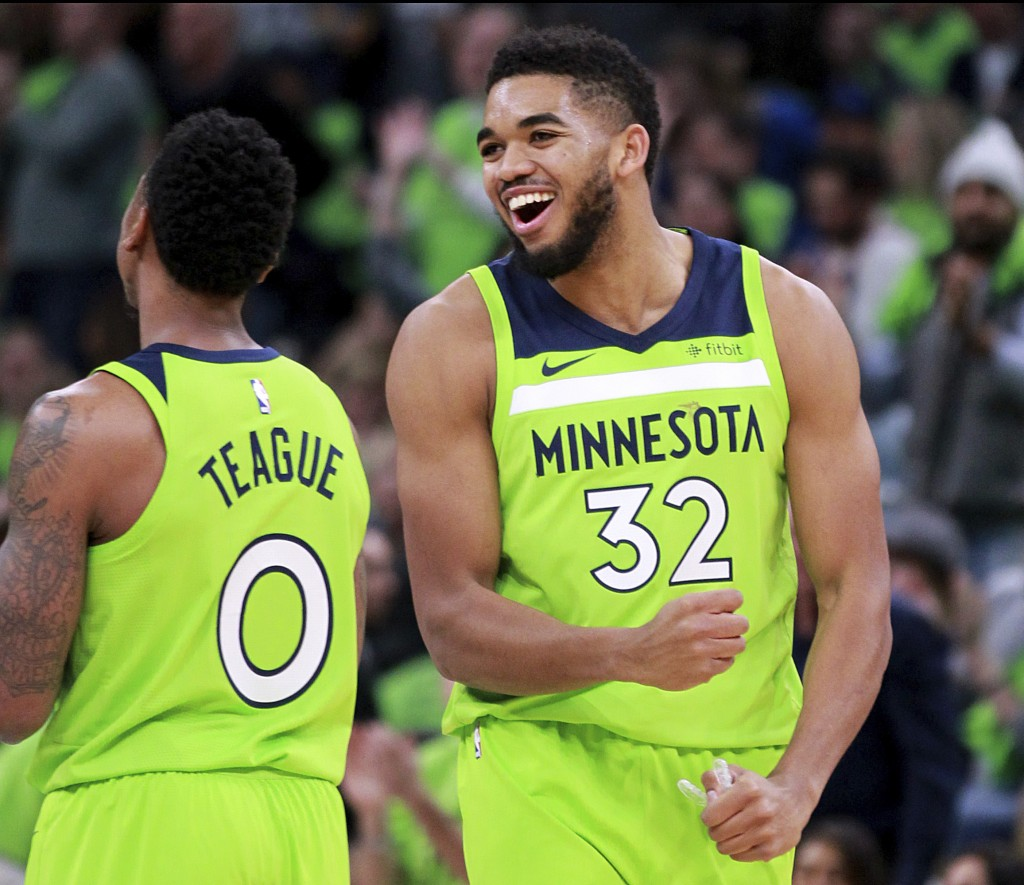 Minnesota Timberwolves center Karl Anthony-Towns (32) and guard Jeff Teague (0) celebrate in the first quarter of an NBA basketball game against the P...