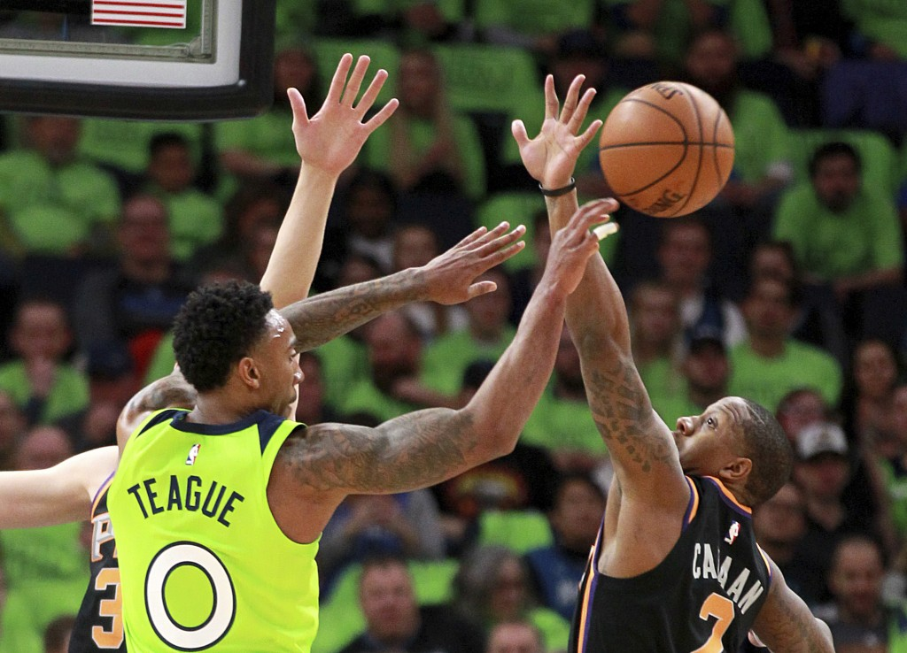 Minnesota Timberwolves guard Jeff Teague (0) throws under pressure from Phoenix Suns guard Isaiah Canaan (2) in the first quarter of an NBA basketball...