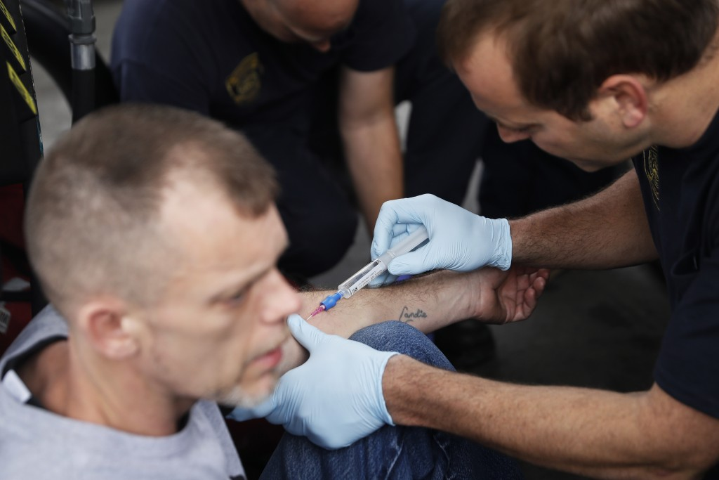 In this Nov. 2, 2017, photo, medics with the Cincinnati Fire Department administer injectable naloxone to a man while responding to a possible overdos...