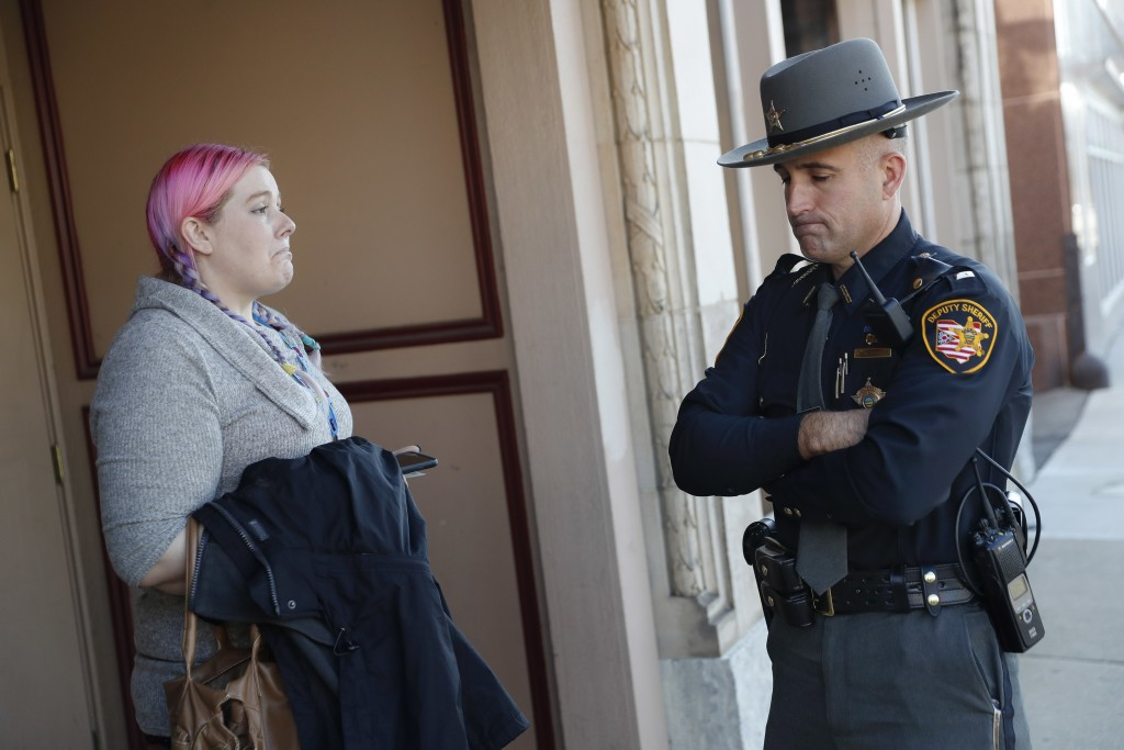 In this Nov. 14, 2017, photo, Lieutenant Morgan Dallman of the Butler County Sheriff's Office, right, reacts while speaking to a friend of a suspected...