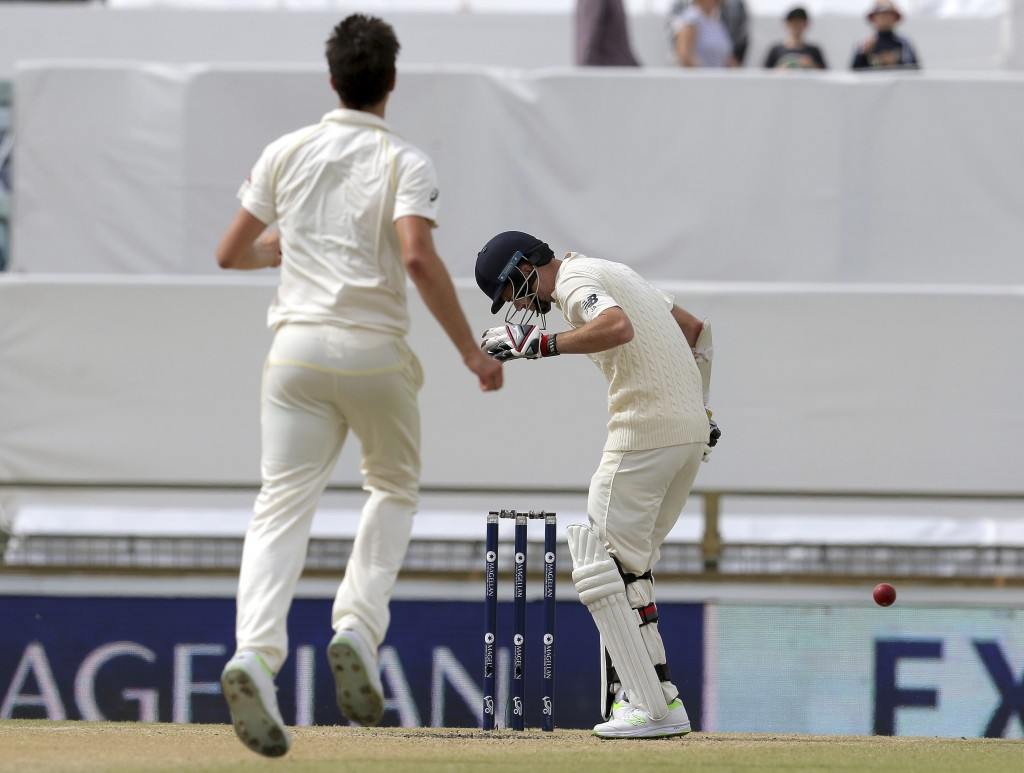 England's James Anderson, right, bends over after he is hit on the helmet by Australia's Pat Cummins, left, during the final day of their Ashes cricke...
