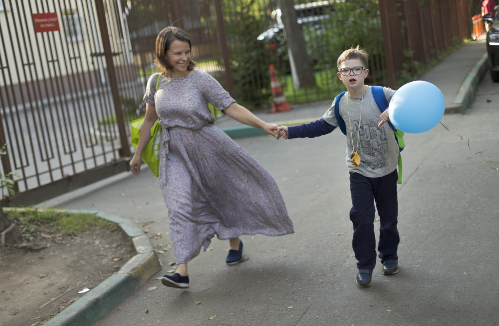 Volunteer Valentina and former 11-year-old pupil Gleb walk home after visiting the St. Sophia orphanage in Moscow, Russia, on Tuesday, Sept. 12, 2017....