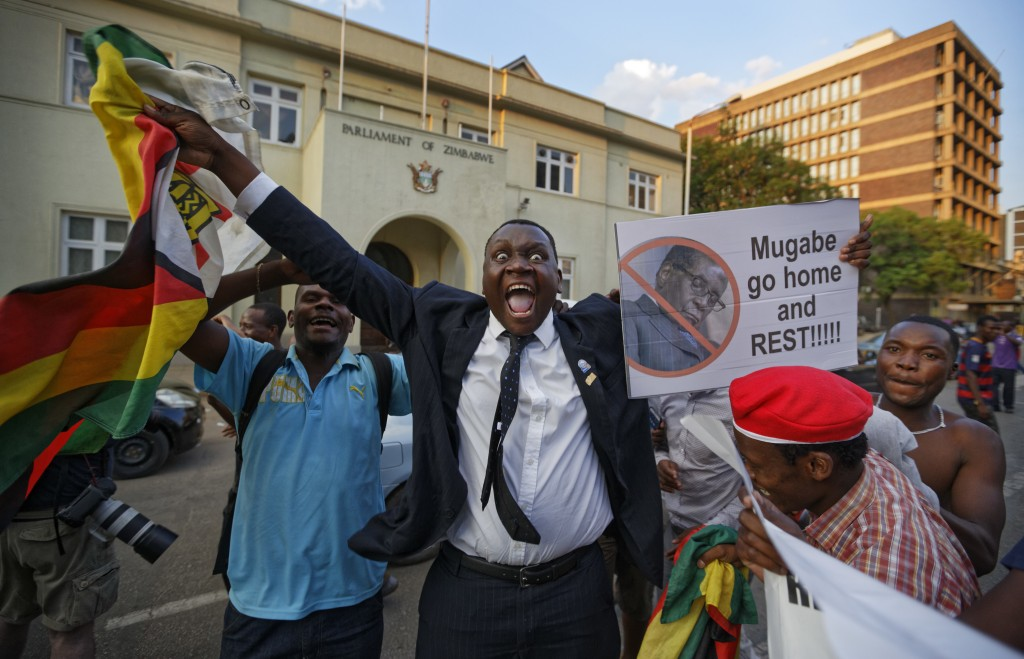 FILE - In this Tuesday, Nov. 21, 2017 file photo Zimbabweans celebrate outside the parliament building immediately after hearing the news that Preside...