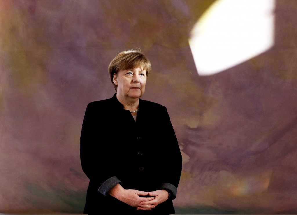 FILE - In this Friday, Jan. 27, 2017 file photo German Chancellor Angela Merkel watches as Former German Foreign Minister Frank-Walter Steinmeie and h...