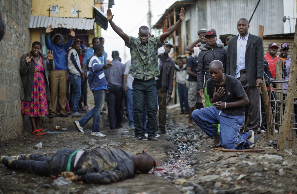 FILE - In this Wednesday, Aug. 9, 2017 file photo residents hold their hands up in the air towards police, as a man genuflects, right, next to the bod...