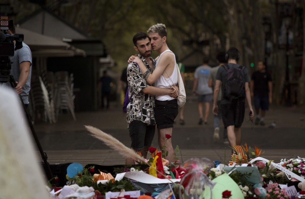 FILE - In this Monday, Aug. 21, 2017 file photo two men look at flags, messages and candles placed on the ground after a van attack that killed at lea...