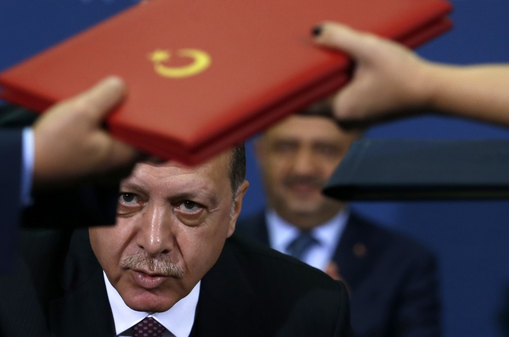 FILE - In this Tuesday, Oct. 10, 2017 file photo Turkey's President Recep Tayyip Erdogan looks on as documents are exchanged after the signing of an a...